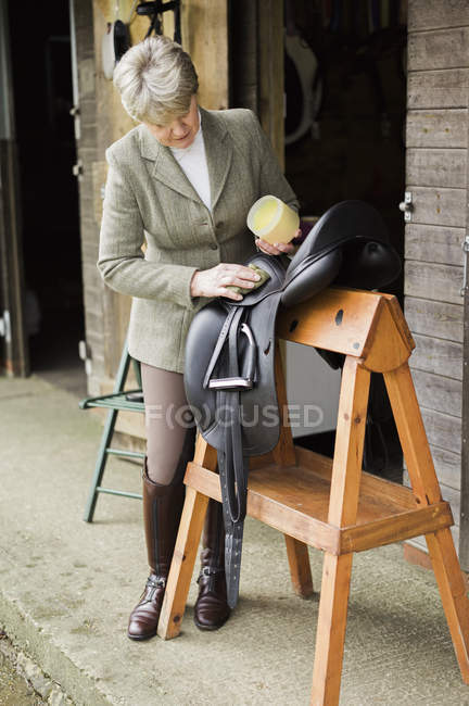 Frau putzt und bereitet Sattel und Sattel vor — Stockfoto
