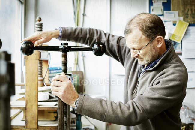 Uomo che usa una pressa per libri — Foto stock