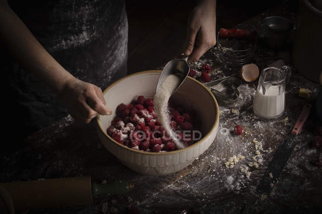 Жінка, додавши цукор у свіжою малиною — стокове фото