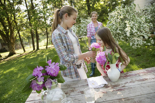 People gathering flowers and arranging together — Stock Photo