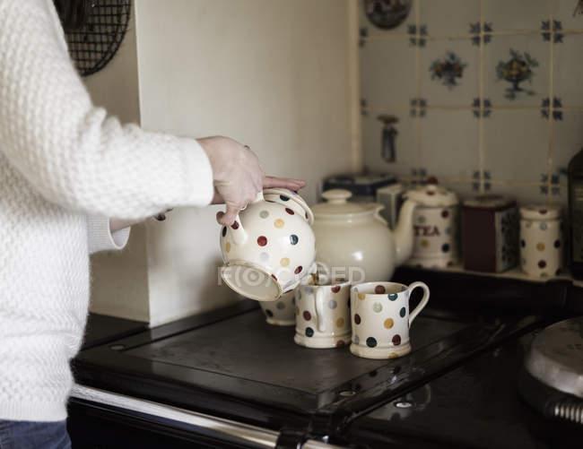 Mains féminines verser le thé dans la tasse — Photo de stock
