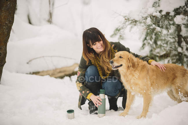 Woman stroking a dog — Stock Photo