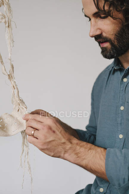 Male artist stitching and weaving with thread. — Stock Photo
