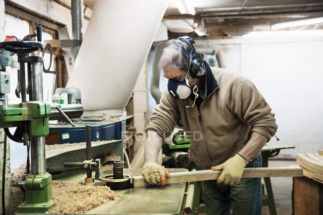 Uomo che lavora su un pezzo di legno — Foto stock