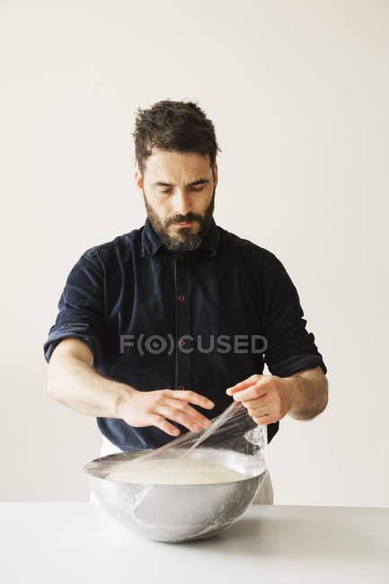 Baker, cobrindo a massa de pão — Fotografia de Stock
