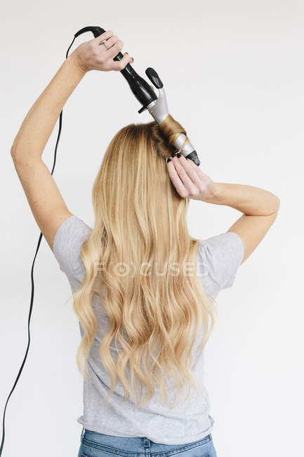 Woman with blond hair using curling tongs — Stock Photo