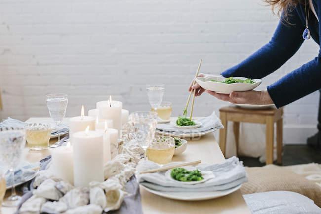 Colocación de plato de comida en la mesa de la mujer - foto de stock