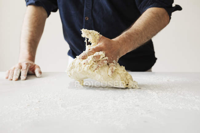 Baker kneading and shaping dough — Stock Photo