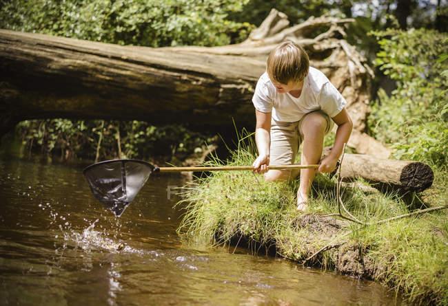 Хлопчик на колінах річки банком — стокове фото