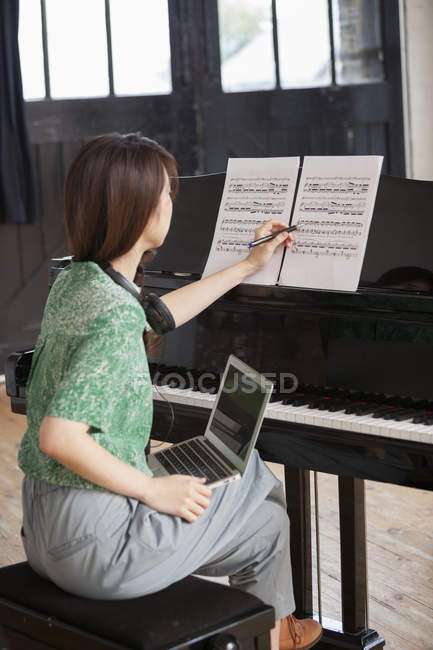 Woman sitting at a grand piano — Stock Photo