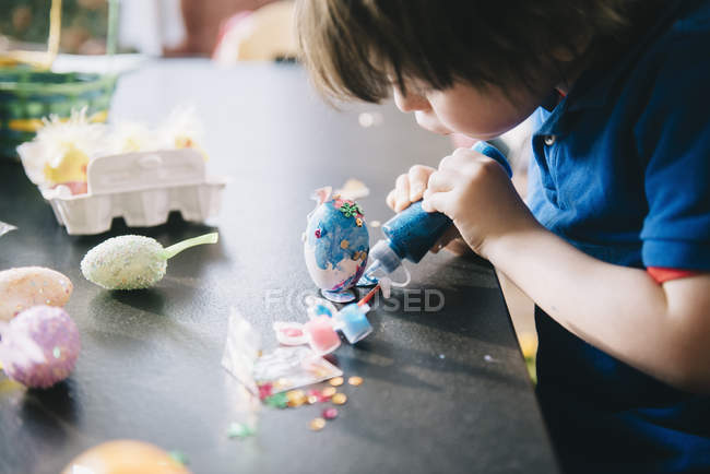 Child decorating eggs at Easter — Stock Photo