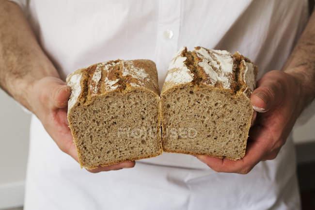 Baker holding a freshly baked loaf — Stock Photo