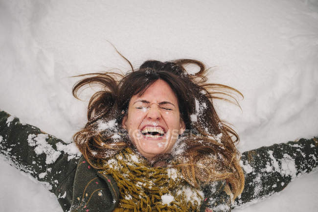 Woman lying on a snow bank — Stock Photo