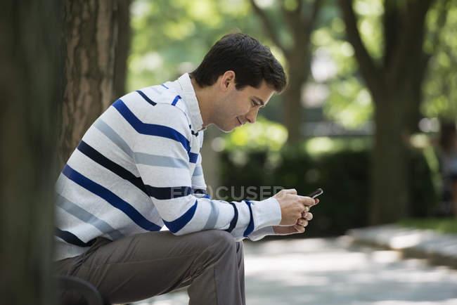 Uomo che controlla smart phone per messaggi — Foto stock