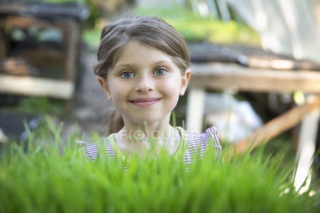 Girl standing smiling by glasshouse bench — Stock Photo