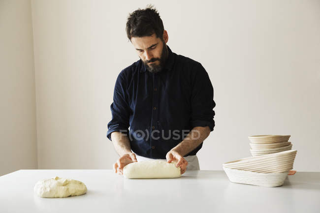 Baker shaping bread dough — Stock Photo