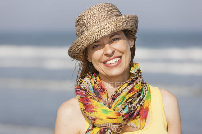 Frau in Sonnenhut und Schal am Strand — Stockfoto