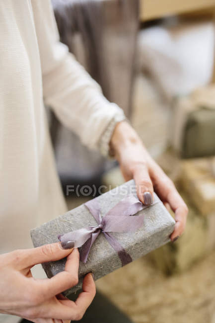 Woman holding gift wrapped present — Stock Photo