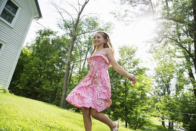 Jeune fille qui traverse l'herbe — Photo de stock