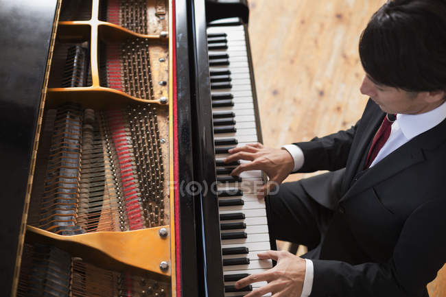 Man playing on a grand piano — Stock Photo