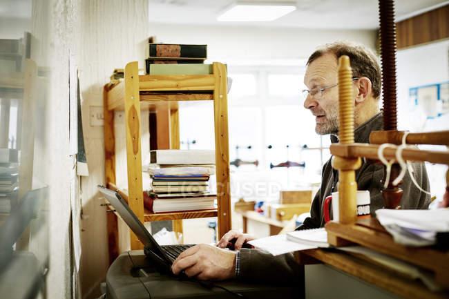 Uomo che utilizza un computer portatile su un'attività di rilegatura . — Foto stock