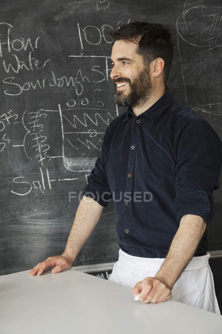 Baker standing in front of a blackboard — Stock Photo