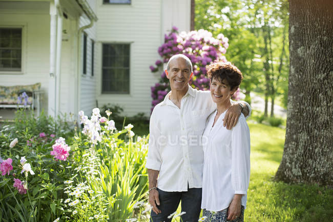 Mature couple standing together among flowers — Stock Photo