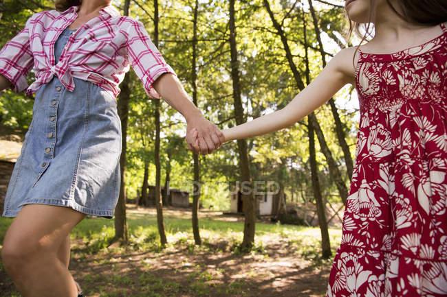 Mulher e menina correndo ao longo de árvores — Fotografia de Stock