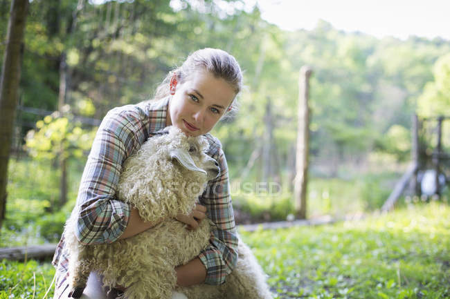 Teenager kneeling and putting arms around goat — Stock Photo