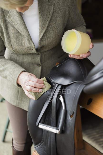 Frau, Reinigung und Vorbereitung Tack und Sattel — Stockfoto