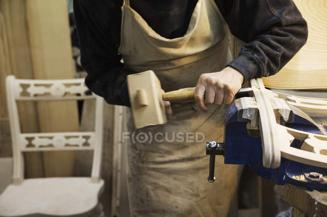 Man working on a wooden chair — Stock Photo