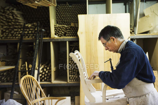 Man working on a wooden chair. — Stock Photo