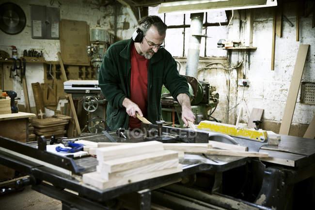 Uomo che lavora in un laboratorio di mobili. — Foto stock