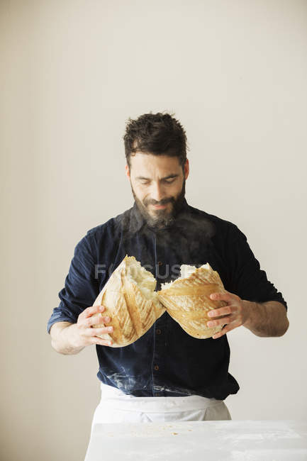 Baker holding a loaf of bread. — Stock Photo