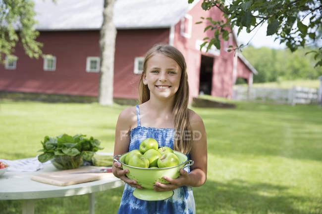 Menina carregando uma tigela grande de maçãs . — Fotografia de Stock