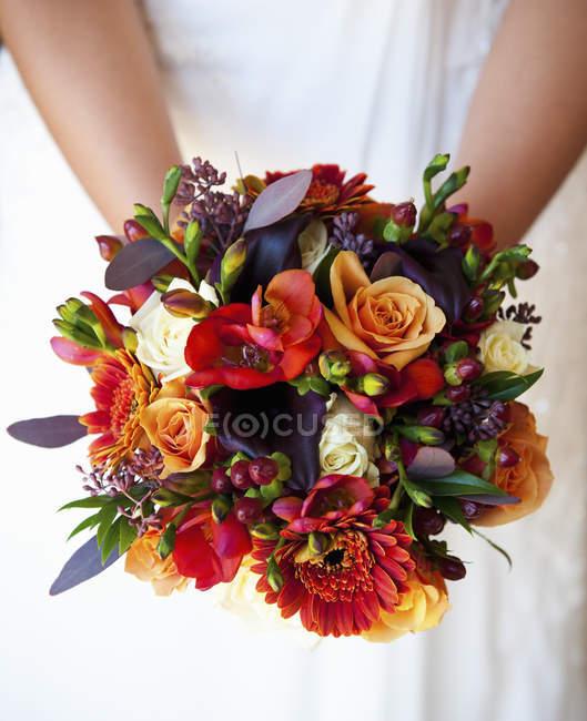 Braut hält Brautstrauß — Stockfoto