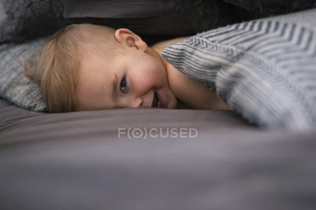Jovem rapaz deitado de bruços — Fotografia de Stock