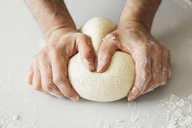 Baker shaping dough into a ball. — Stock Photo
