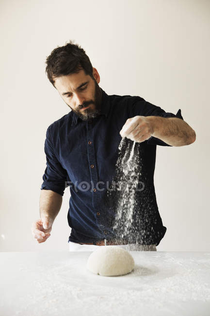 Baker sprinkling flour over bread dough. — Stock Photo