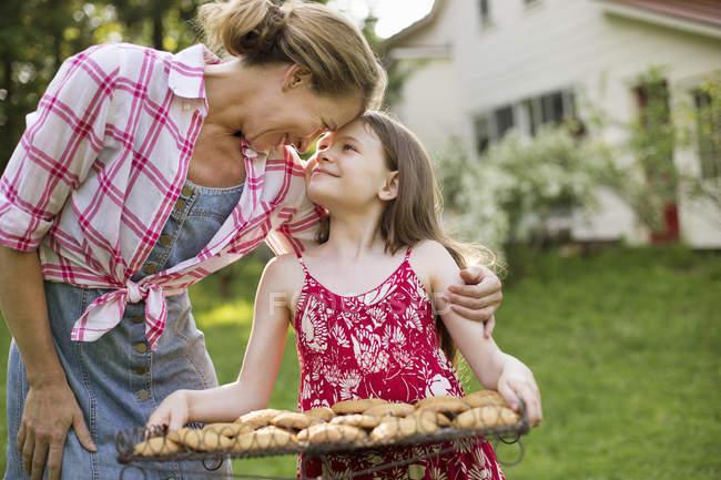 Menina segurando bandeja de biscoitos cozidos frescos — Fotografia de Stock
