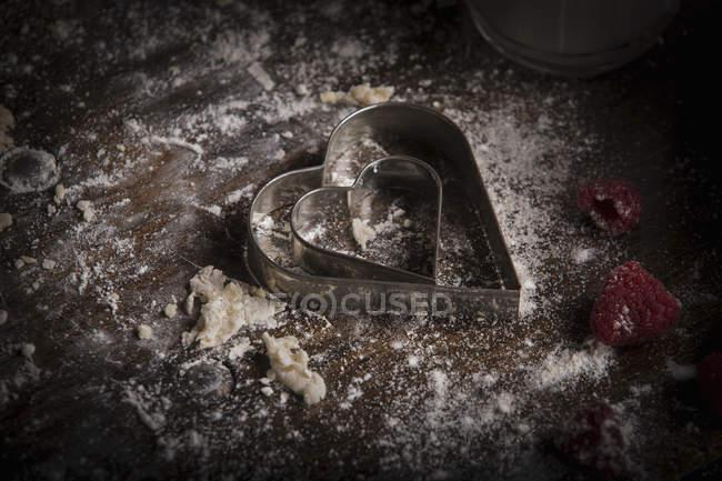 Coupeurs de biscuits en forme de coeur et framboises fraîches — Photo de stock