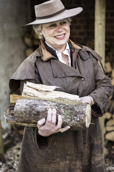 Woman carrying split logs — Stock Photo
