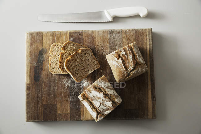 Baked loaf of bread and slices — Stock Photo