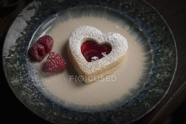 Plate with heart shaped biscuit and raspberries — Stock Photo