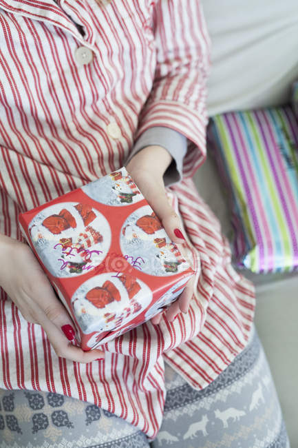 Girl holding a small Christmas present. — Stock Photo