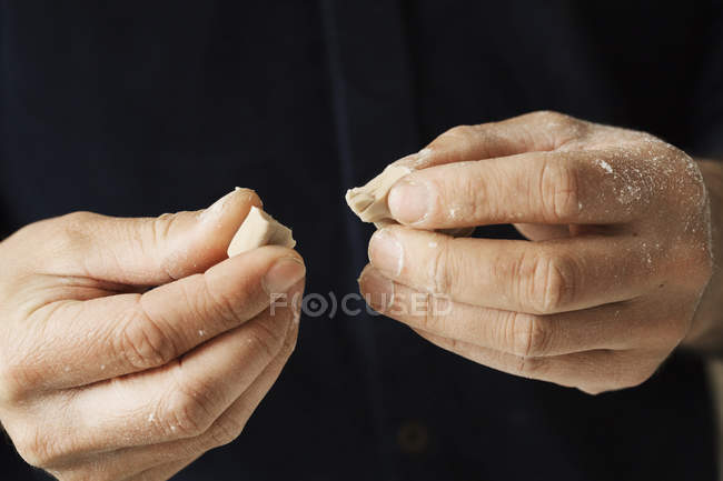 Baker holding pieces of fresh yeast — Stock Photo