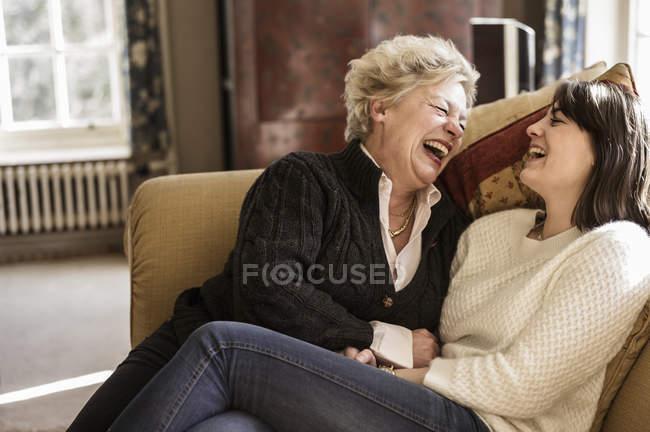 Женщины сидят в диван и смех — стоковое фото