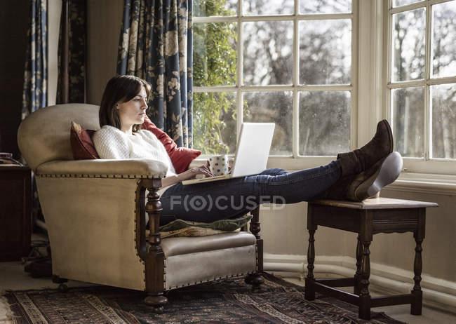 Frau mit laptop zu hause — Stockfoto
