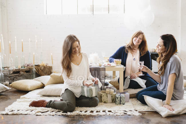 Women at celebration, one opening presents. — Stock Photo