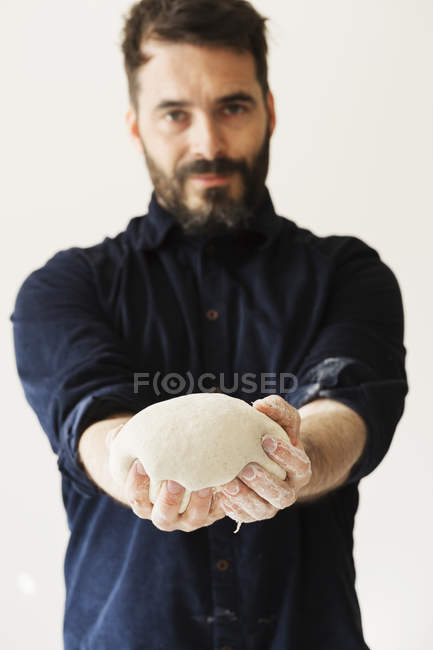 Baker holding a portion of bread dough — Stock Photo